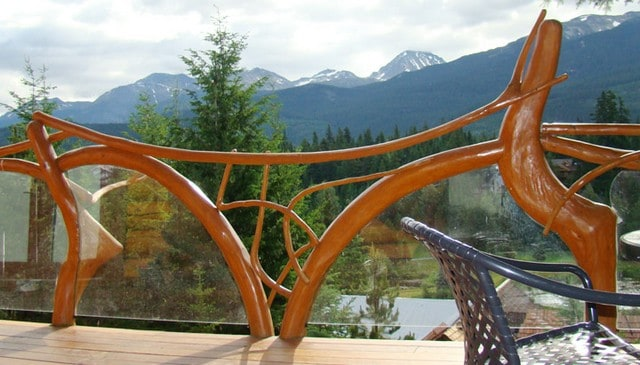 log and branch railing with glass panels